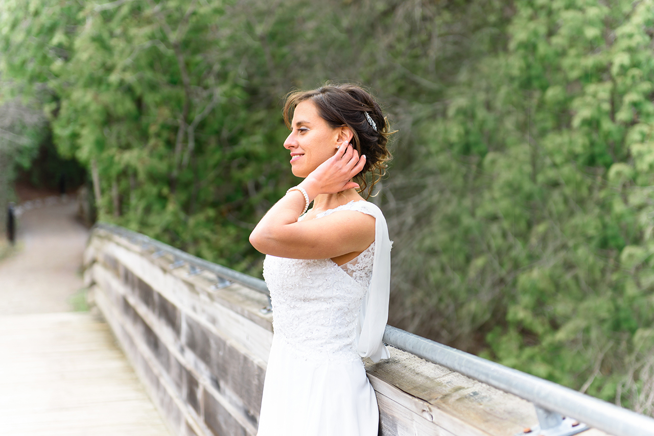 Portrait of the bride standing on the bridge with beautiful green scenery. Wedding pictures taken at Pickering museum village near Ajax