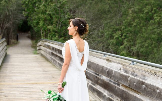 Portrait of the bride standing on the bridge, holding flowers in her hand. Wedding pictures taken at Pickering museum village