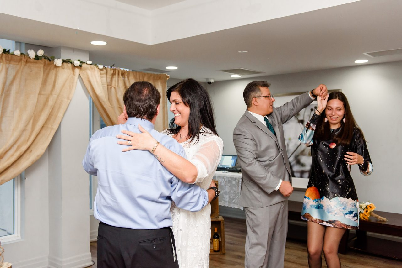bride and groom are dancing with man of honor and bridesmaid