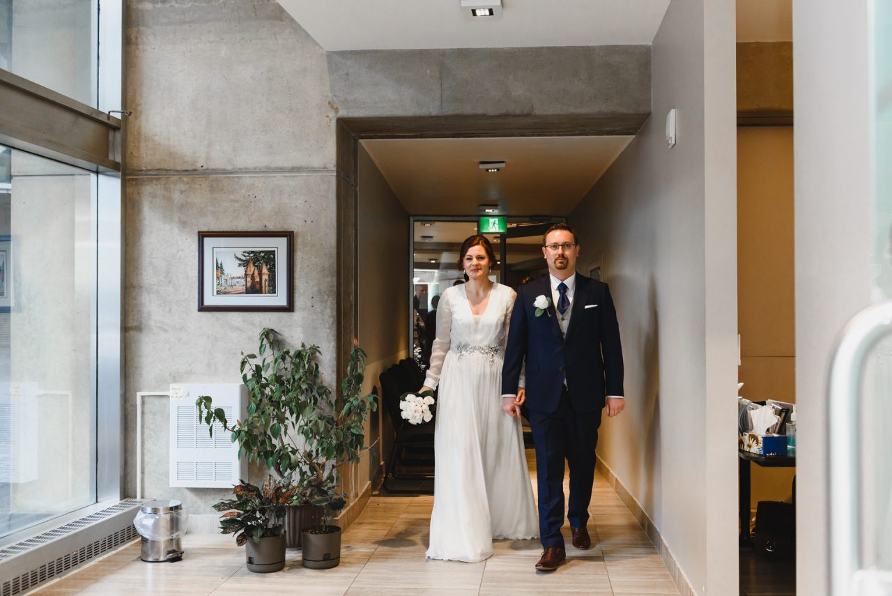 picture of bride and groom walking into City Hall to get married, downtown Toronto