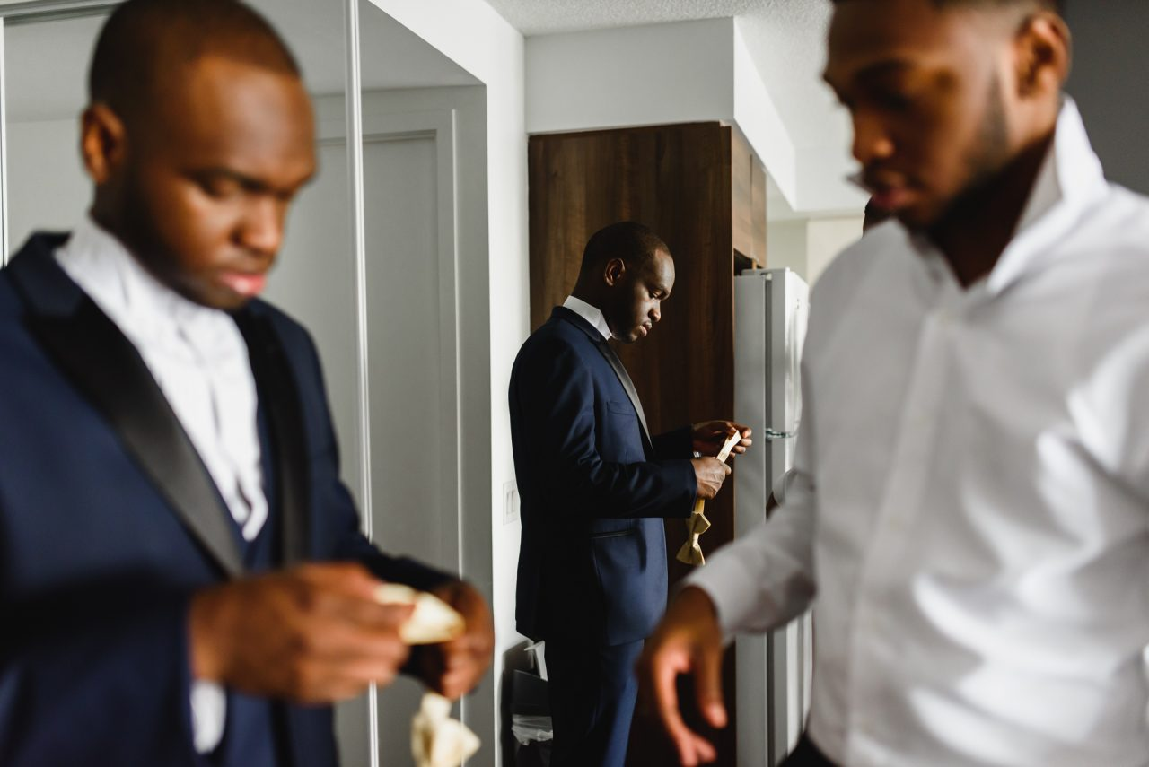groom getting ready at home with best man