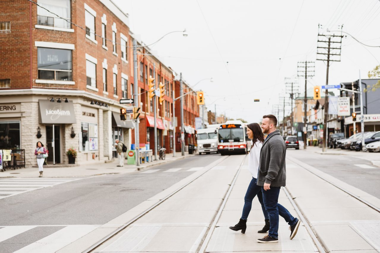 walking down the queen street during the engagemnt photo shoot, Toronto