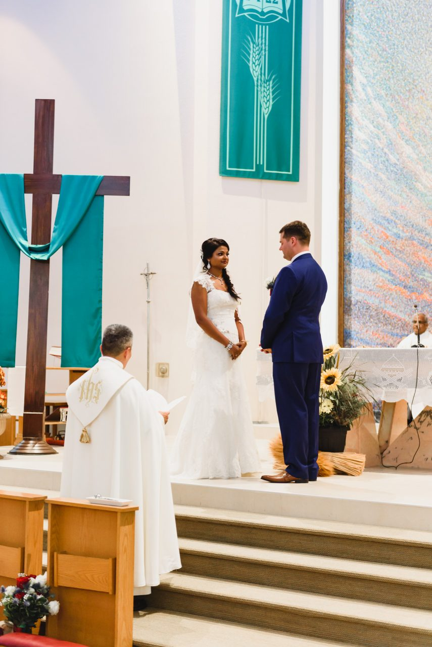 bride and groom during wedding ceremony at wedding ceremony at Our Lady of the Airways Catholic Church